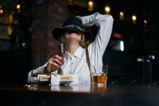 Senior attractive female gangster smoking cigar over dark background in restaurant