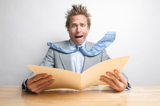 Shocked office worker screaming at the contents of a file folder open on his desk