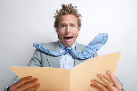 Upset businessman reacting to the contents of a file folder