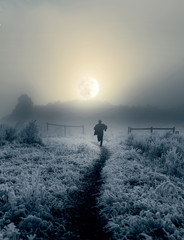 Foto op Canvas Bleke violet Dramatic artistic image of man running toward rising moon in winter landscape