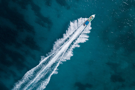 Bird eye view of motor boat with wake at sea