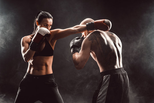 Woman exercising with trainer at boxing and self defense lesson, studio, smoke on background. Female and male fight