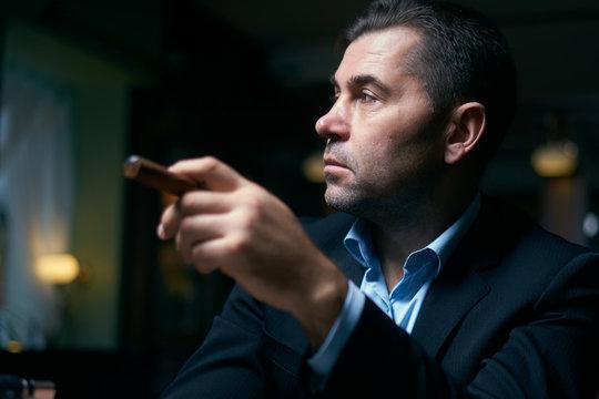 handsome man smoking cigar in a lounge bar