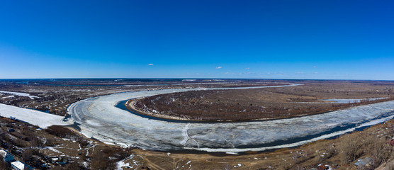 Winding ice-covered river and blue sky. Panoramic aerial view