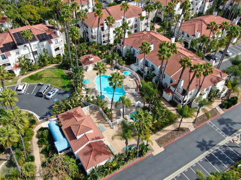 Aerial view of typical Southern California Spanish style residential condo, surrounded by nice garden with trees and swimming pool. San Diego, California, USA