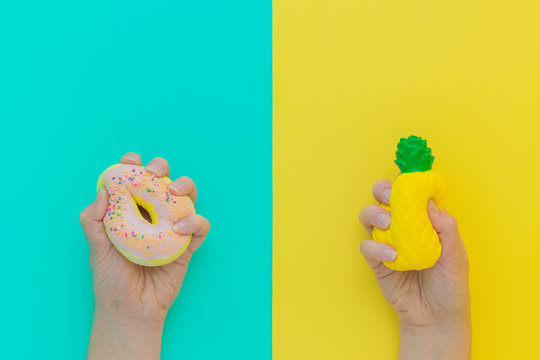 Flat lay antistress squish toys yellow pineapple,pink donut with sprinkles in hands.Bright blue background.Compressing,soft,squeezable items to relieve stress,problem,anxieties,worries.Summer concept