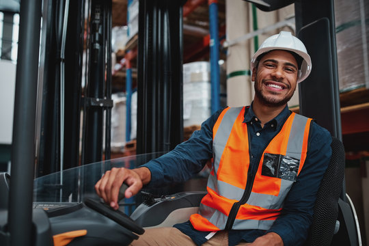 Young forklift driver sitting in vehicle in warehouse smiling looking at camera