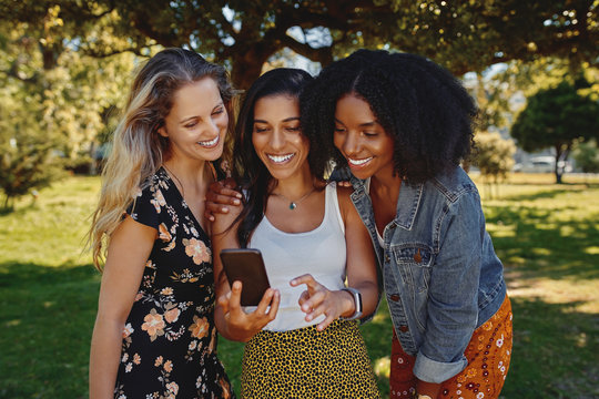 Portrait of a group of diverse young female friends watching something on smart phone in the park