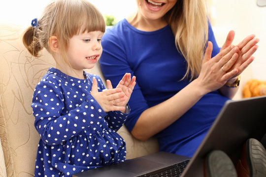 Cute little girl on couch with mom use laptop pc for chat with her dad away on business portrait. Point finger hand in display social web network bank mortgage credit wireless ip telephony concept