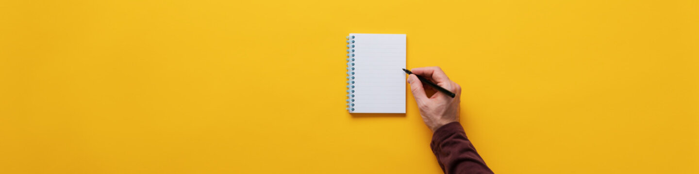 Male hand writing in notepad