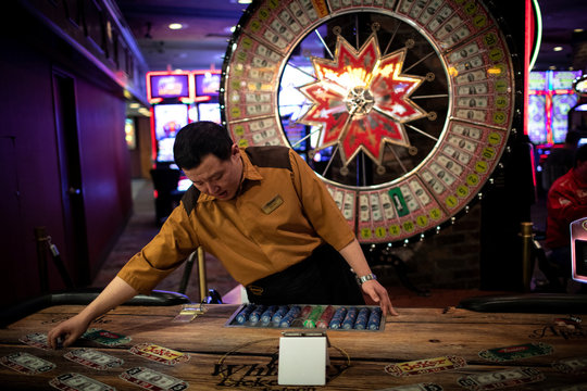A worker mans a roulette wheel game at a casino on Freemont Street in Las Vegas