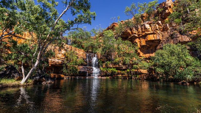 Landscape view of tourists swimming in the plunge pool of Galvin's Gorge on the Gibb River Road in the Kimberley Region of Western Australia.