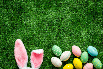 Easter concept. Eggs, Bunny's ears on green grass background top-down copy space