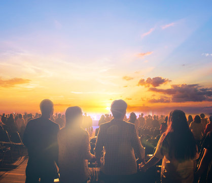 silhouettes of concert crowd in front of sunset background