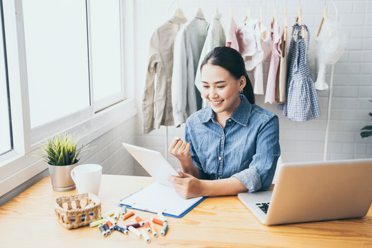 Entrepreneurs small business owner,Asian women Fashion designer drawing new sketches collection,sent a business e-mail to client.sales success,working using laptop,digital smartphone in workshop