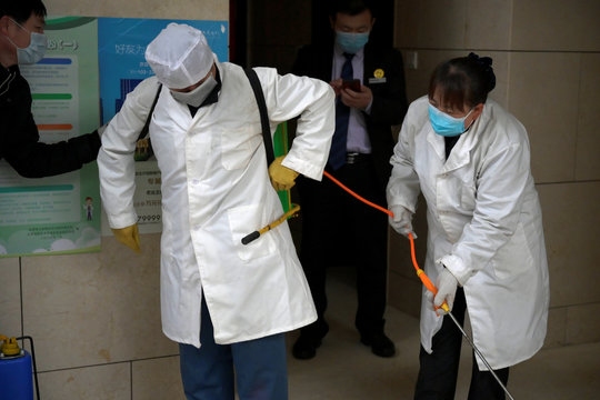 Worker Gong Lixia helps her colleague Wang Fu to put on the disinfectant liquid backpack as they sanitise a residential compound, following an outbreak of the novel coronavirus in the country, in Beijing