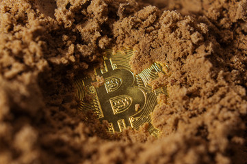 Bitcoin coin mined from the sand Fototapete