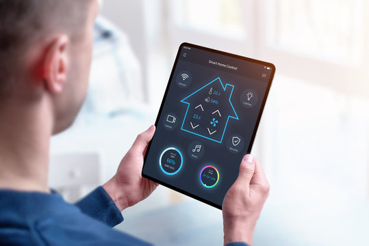 Man holding smart home control tablet with modern app concept