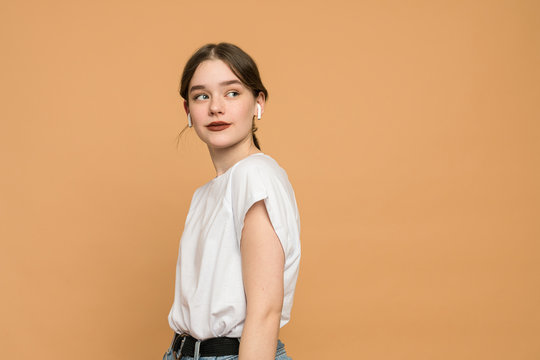 Closeup of a young brunette woman in wireless earphones dressed in white t-shirt, student listening to the music and looking away isolated over orange background with copyspace