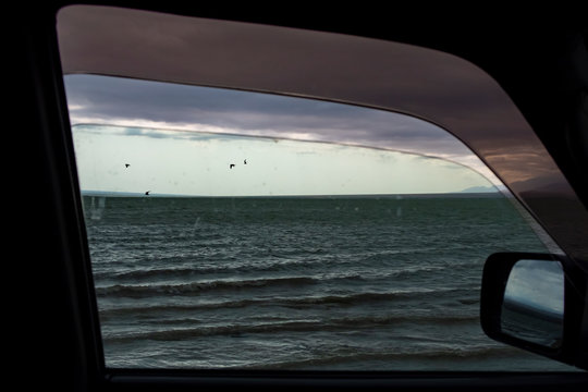 View to the strormy lake from inside  of the car.