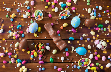 easter, sweets and confectionery concept - chocolate eggs, bunny and candy drops on wooden background