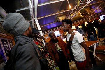 Kenyan standup comedian Brian Onjoro speaks to his colleagues after his performance at the Kez's Kitchen restaurant in Nairobi