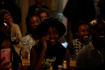 A woman in the audience laughs during a standup show by Kenyan comedian Brian Onjoro at the Kez's Kitchen restaurant in Nairobi