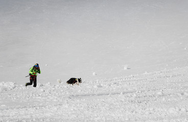 An Italian alpine rescuer and rescue dog run across snow during an avalanche rescue training exercise
