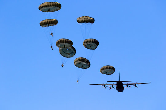 Military parachutist paratroopers jumping out of an air force airplane.