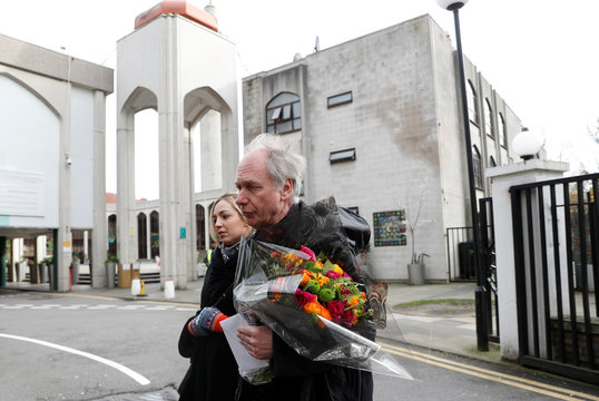 Reverend Dr Anders Bergquist of St. John's Wood church brings flowers at the London Central Mosque in London