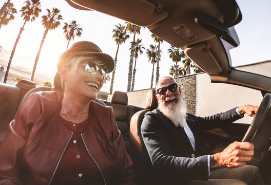 Senior trendy couple inside a convertible car on holiday time - Mature rich people having fun doing a road trip during vacation - Travel, fashion and joyful elderly concept - Main focus on