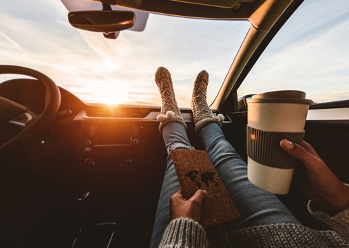 Woman drinking coffee paper cup inside car with feet warm socks on dashboard - Girl relaxing in auto trip reading travel book with snow mountains in background - Traveler concept - Focus on feet