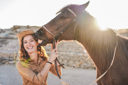 Young farmer woman playing with her horse in a sunny day inside corral ranch - Concept about love between people and animals - Focus on girl face