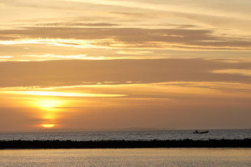 The sun rises as a boat heads across Apalachicola Bay toward the oyster bars and a day of harvesting shellfish off Eastpoint, Florida