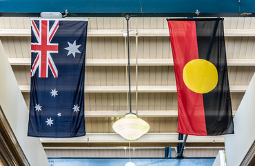 Australian and Australian Aboriginal national flags are hanging in a Melbourne building with a white painted wooden roof.