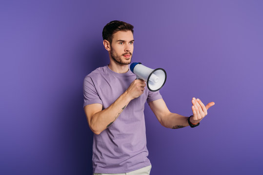 serious young man showing come here gesture while holding megaphone on purple background