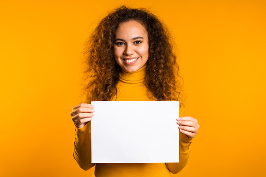 Pretty curly woman holding horizontal white a4 paper poster. Copy space. Smiling trendy girl on yellow background.