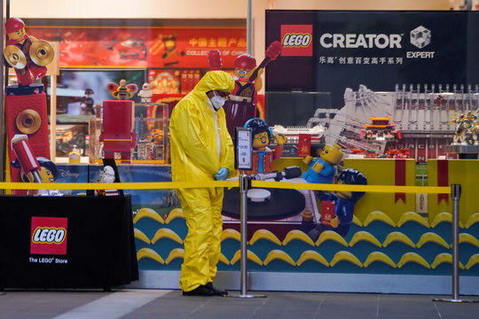 A health worker stands outside a Lego store at a main shopping area, in downtown Shanghai