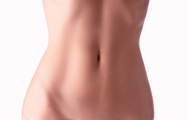 Close up of slim young woman belly isolated on white.