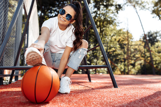 Stylish brunette young woman dressed in casual modern clothes posing with basketball at the stadium.
