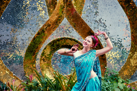 Beautiful young caucasian woman in traditional indian clothing sari with bridal makeup and jewelry and henna tattoo on hands dancing in temple garden.