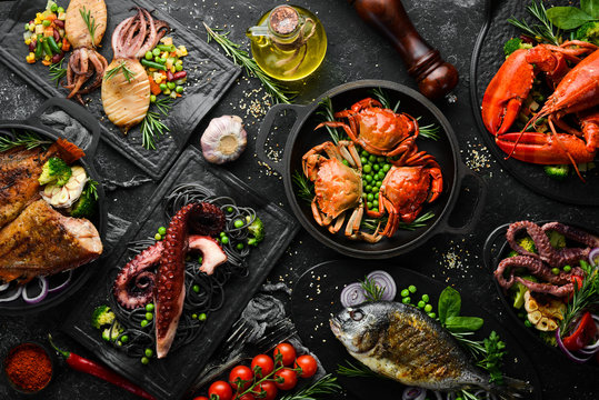Set of seafood dishes. Fish, squid, octopus on a black stone background. Top view. Free space for your text.