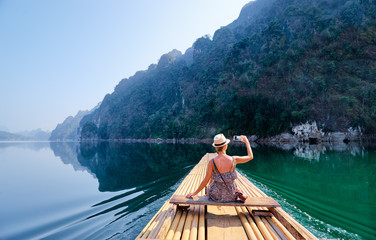 Travel and technology. Pretty young woman taking photo on smartphone sailing National Park lake on...