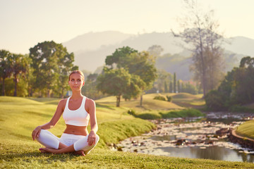 Garden Poster Lotus flower Yoga at park with view of the mountains, with sunlight. Young woman in lotus pose sitting on green grass. Concept of calm and meditation.