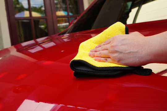 a woman hand polish the red car hood with yellow towel after waxing the car for shiny look ,manual car wash and hand wash at home by woman concept
