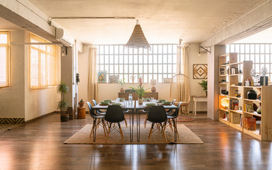 Interior design / decoration. Spacious dining room in bright industrial loft with shelves, chairs and a table set ready for a nice meal.