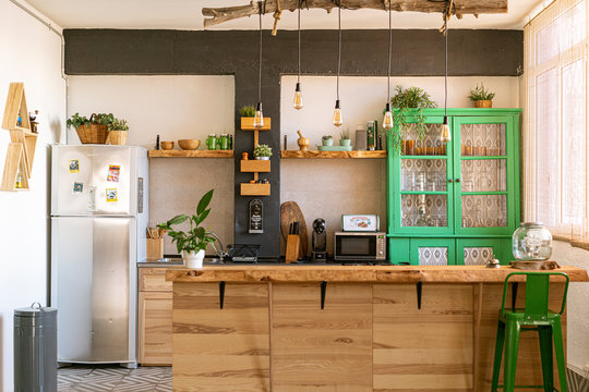 Beautiful, stylish and open bright kitchen with wooden kitchen island, green cabinet, big windows and plants.