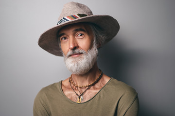 Style and vacation concept. Studio portrait of handsome senior man with gray beard and hat.