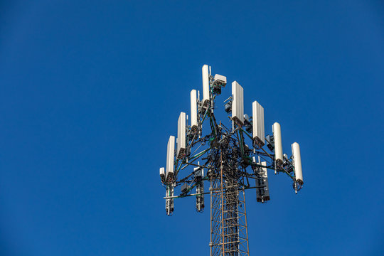 Closeup view of wireless cellphone antenna tower. Telecommunication equipment isolated on deep blue sky background. Concept of communication technology and service provider coverage area
