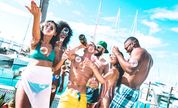 Multicultural friends group having fun drinking wine at sail boat party - Entertainment concept with young multi racial people on sailboat - Happy travel lifestyle on luxury location - Azure filter